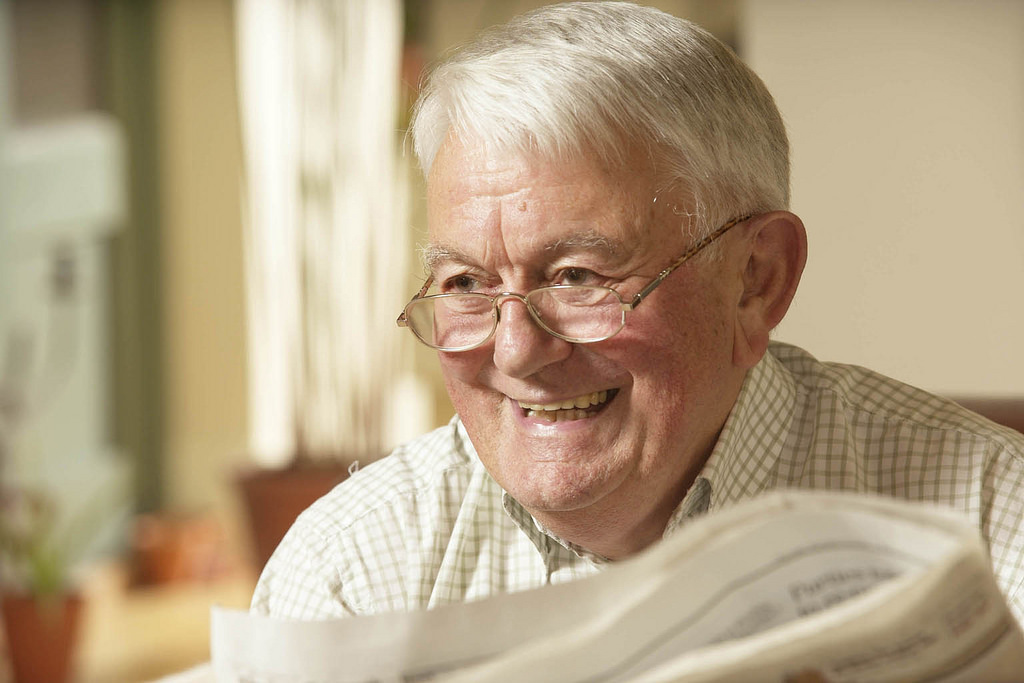 Senior man reading newspaper and smiling